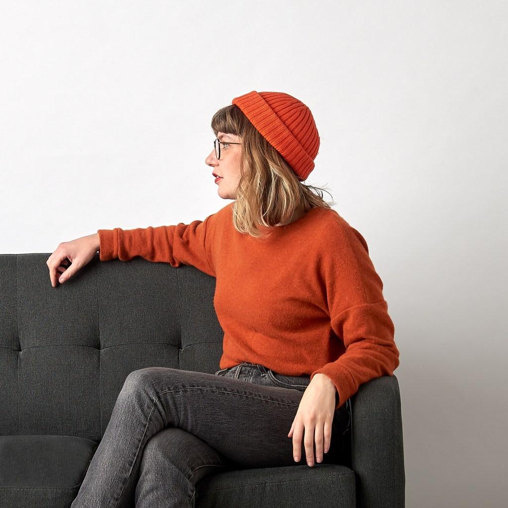 ruby rose wearing a rust orange jumper