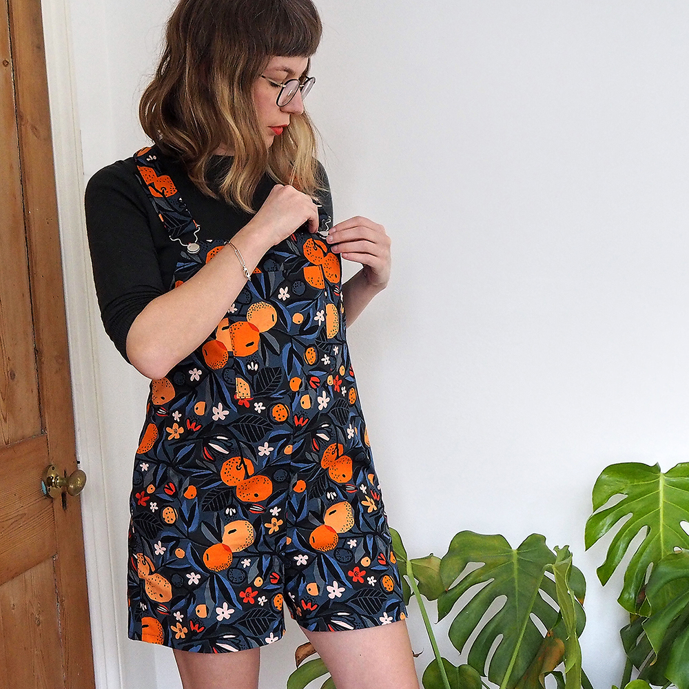 Ruby Rose fastening buckles on orange print shorts dungarees