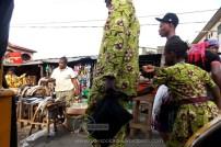 father dragging child through market