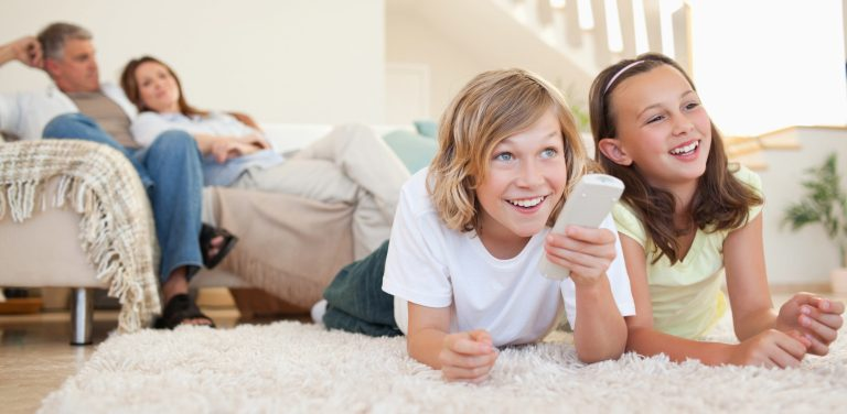 Siblings lying on the floor watching tv together