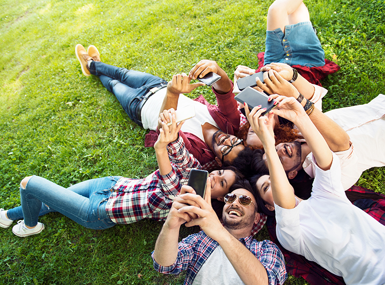 Group of young people laying on the grass in circle, using phone