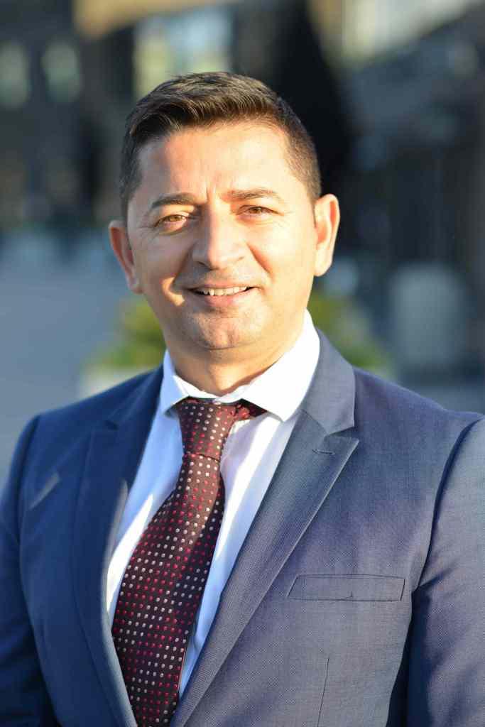 Tony Selimi smiles to camera in a blue blazer and burgundy tie