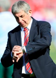 British and Irish Lions' coach Ian McGeechan checks the time as he waits for the start of their international rugby test match against South Africa at the Loftus Versfeld stadium in Pretoria June 27, 2009. REUTERS/Dylan Martinez (SOUTH AFRICA SPORT RUGBY)
