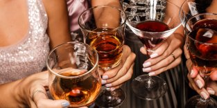 Group of female friends toasting with beverages in nightclub at a party celebration.