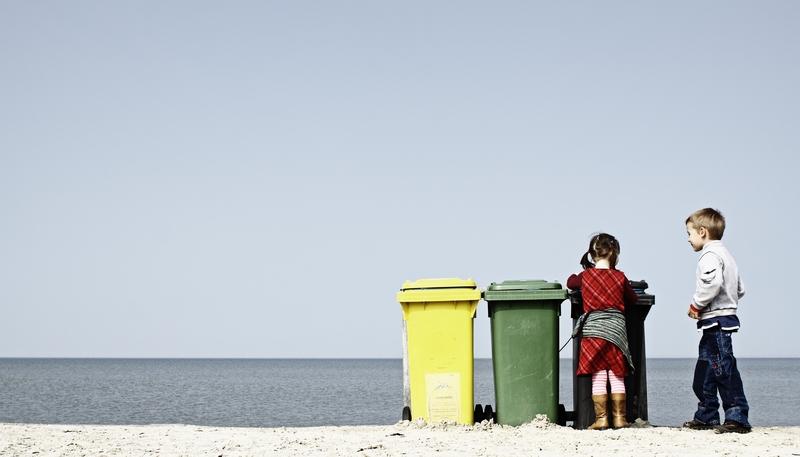 Kinder vor farbigen Mülltonnen am Strand