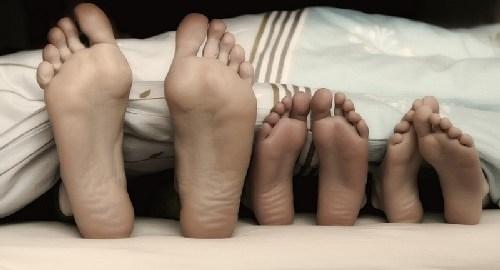 Kleine und große Füßer unter einer Bettdecke