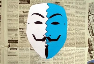 Zweifarbig zerissenes Guy Fawkes Maske auf Zeitungspapier