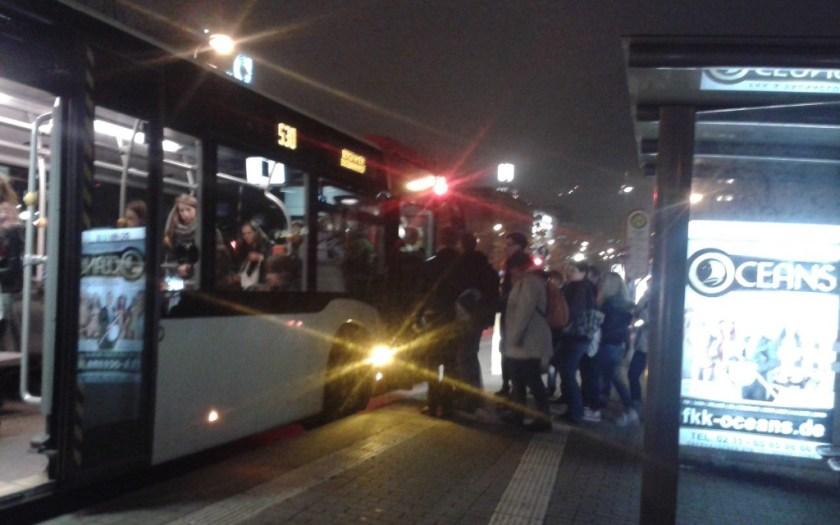 Fahrgäste steigen in einen Bus bei Nacht.