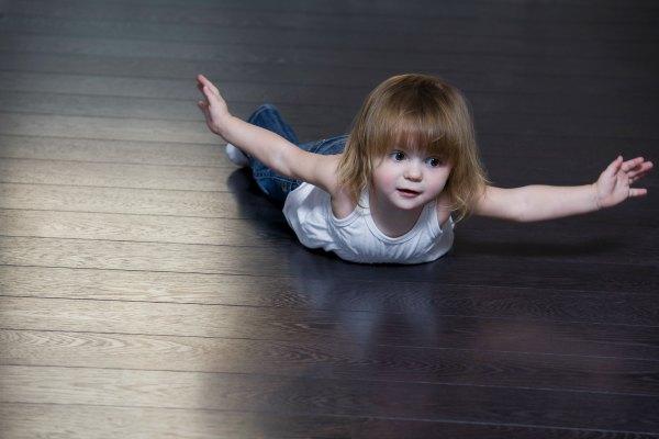 Little girl lying on floor and doing exercises