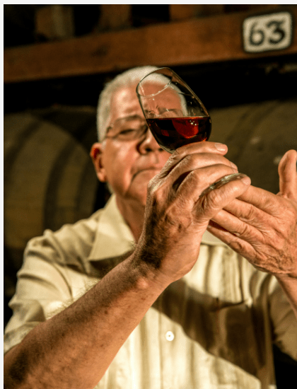 A person drinking a glass of wine  Description automatically generated with low confidence