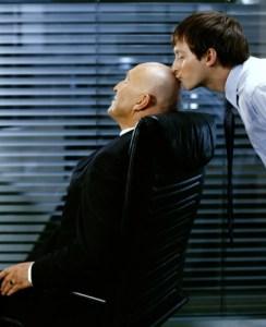 Man kissing mature man's bald head