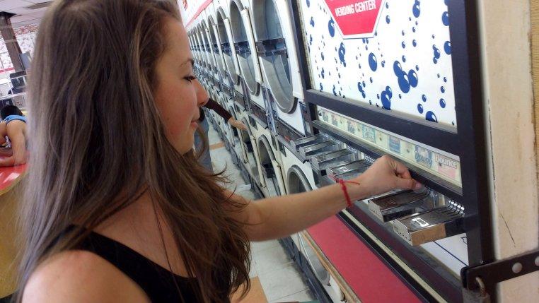 Terézia Ligačová puts quarters in a vending machine that dispenses small packets of soap
