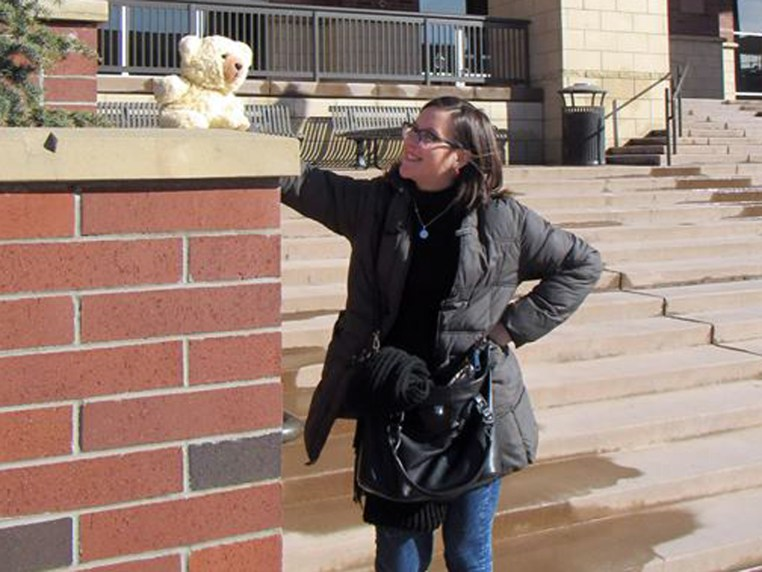 Ludmila and Ambyr Noelle (a plush bear) outside a campus building