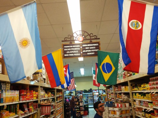 Davis in a grocer market aisle, lined by the flags of Latin American countries