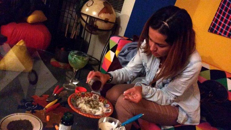 Gizem generously sprinkling ground sumac on her plate of manti!