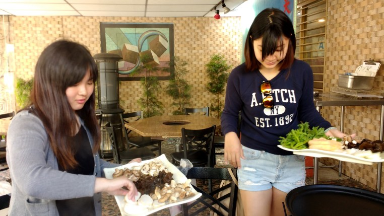 Joey & Ada putting ingredients into our Hot Pot!