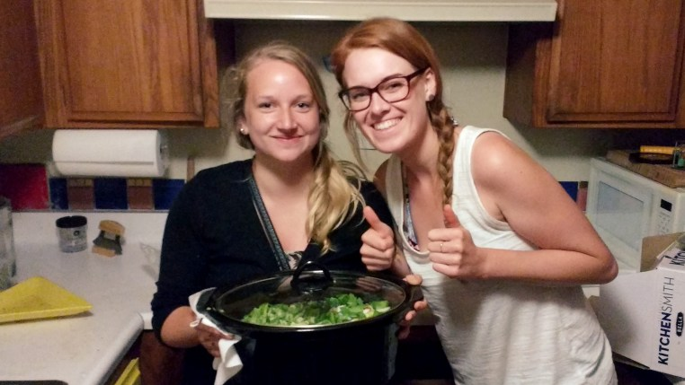 Sarah & Paulina holding a large slow-cooker filled with vegetables