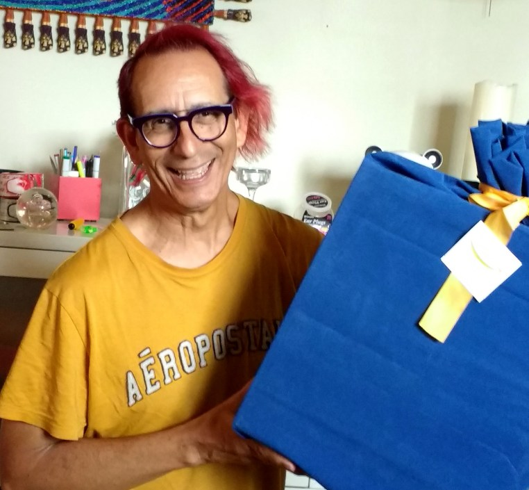 Glenn Zucman holding a large box in blue velvet wrapping and with a large yellow bow