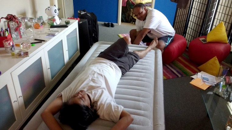 Dharma lying on an air mattress and Kamal finishes inflating it
