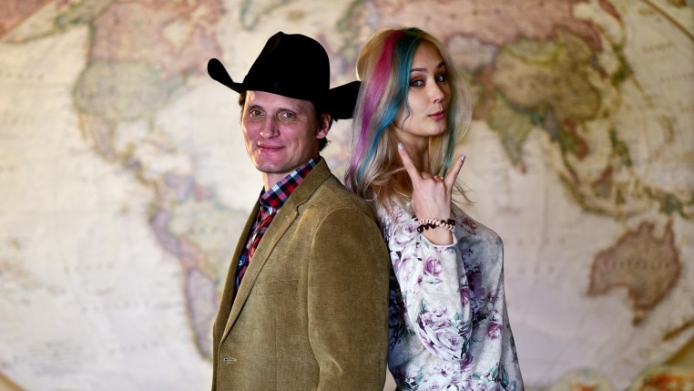 "Samuel Goldman in a tan jacket and a black cowboy hat stands back to back with Olga Usmanova who has platinum hair with pink and blue streaks and gives the heavy metal ""horns"" sign"