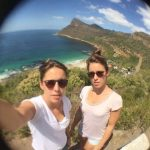 Elise & Lana taking a wide-angle selfie on a coastal cliff