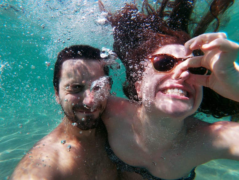 two people underwater with bubbles all around them. One is pinching her nose with her fingers and wearing sunglasses as her hair floats in the clear, turquoise water