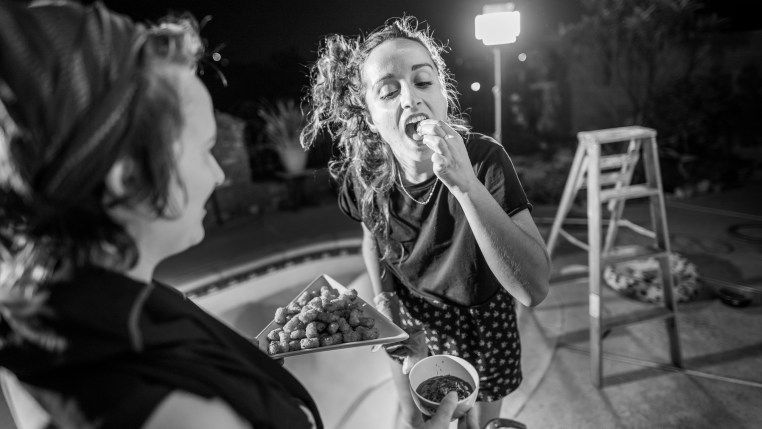Meri tastes a tater tot from a tray offered by Ophelie