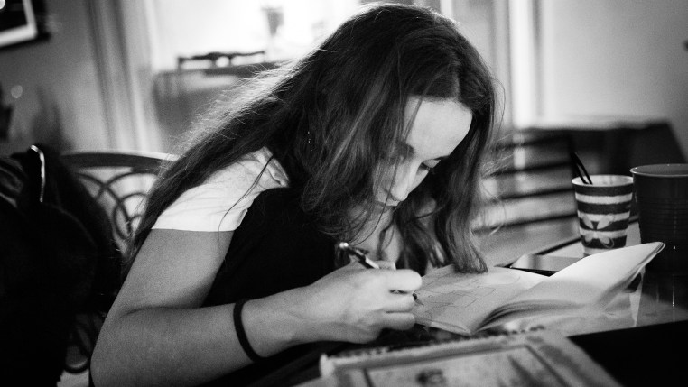 """Merijein Saperas drawing a sketch in a notebook for a """"RULA Mural"""" she will paint the next day."""