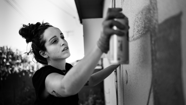 Merijein Saperas painting a mural on a wall using Montana 94 spray paint