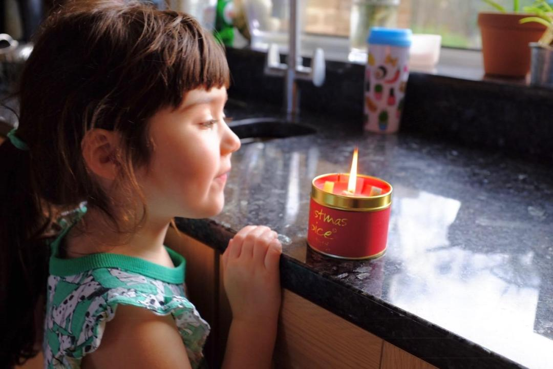 girl looking at a christmas candle
