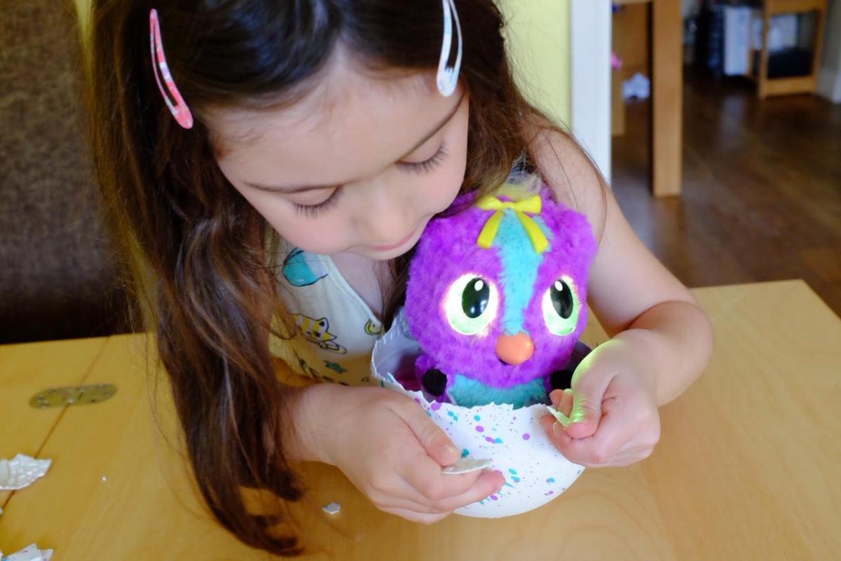 Girl pulling shell off Hatchimals HatchiBabies egg