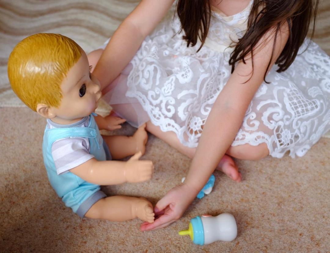 girl ticking Luvabeau doll's feet