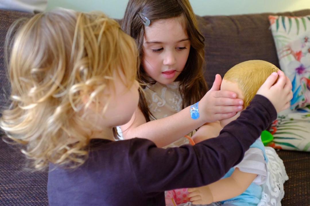two girls playing peekaboo with Luvabeau doll