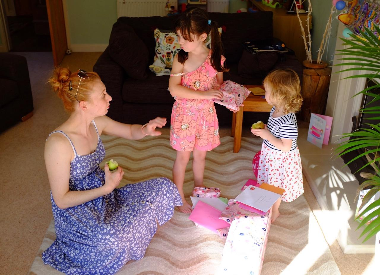Mum with her two girls opening presents