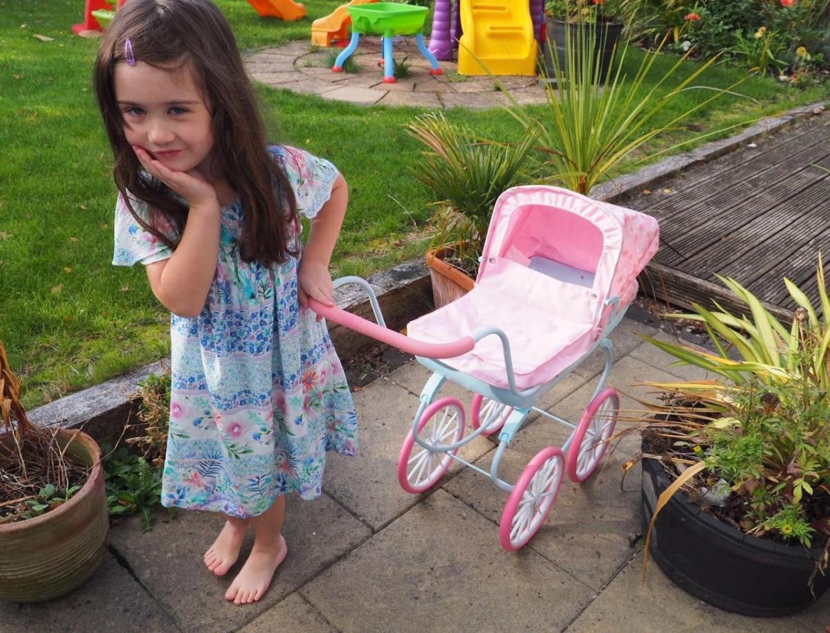 girl playing with baby annabell pram