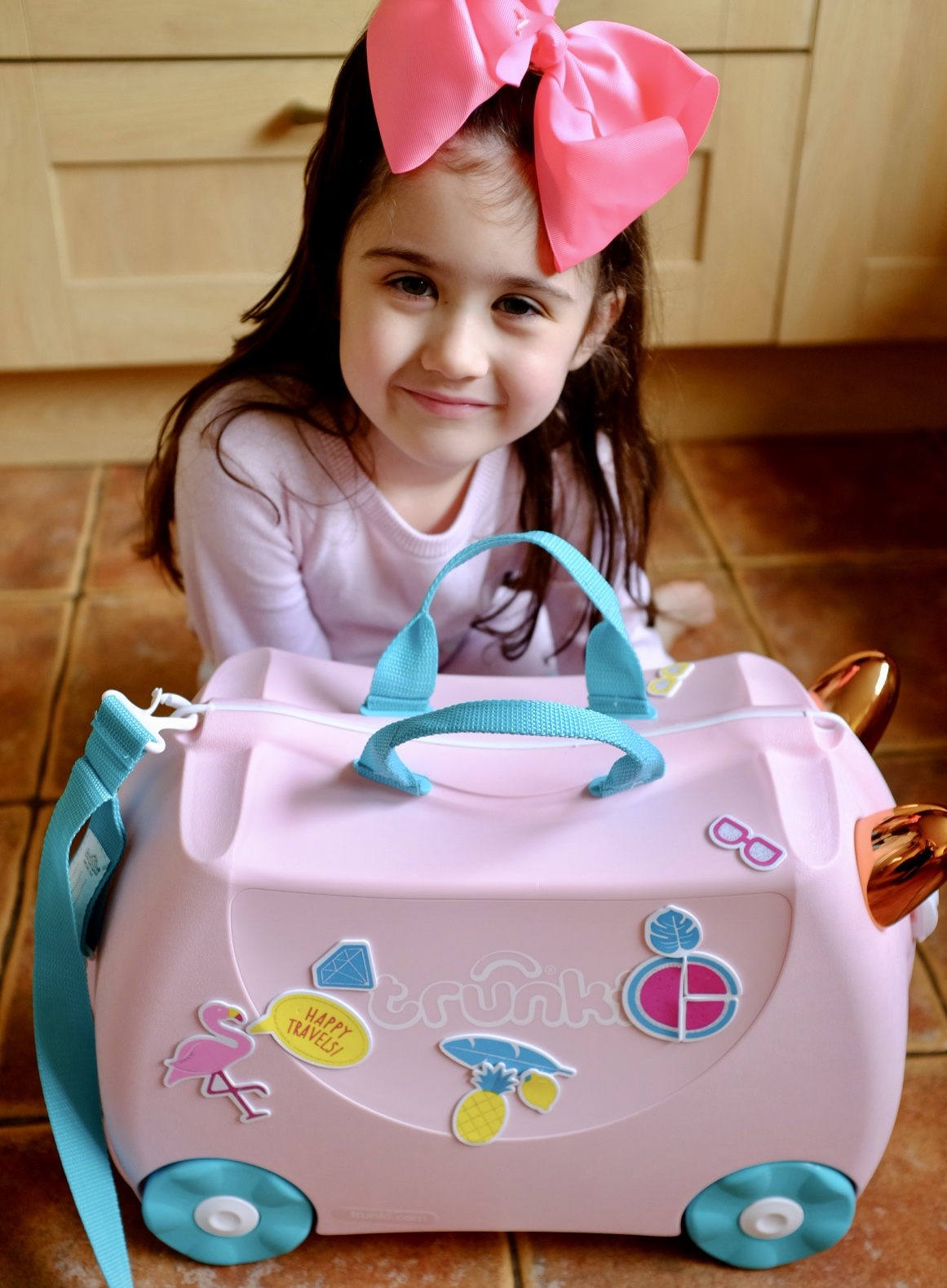 girl with Flossi the Flamingo Trunki