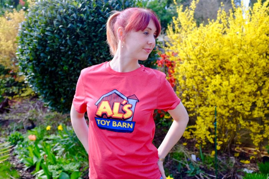 red head wearing an Al's toy barn tee from shopDisney