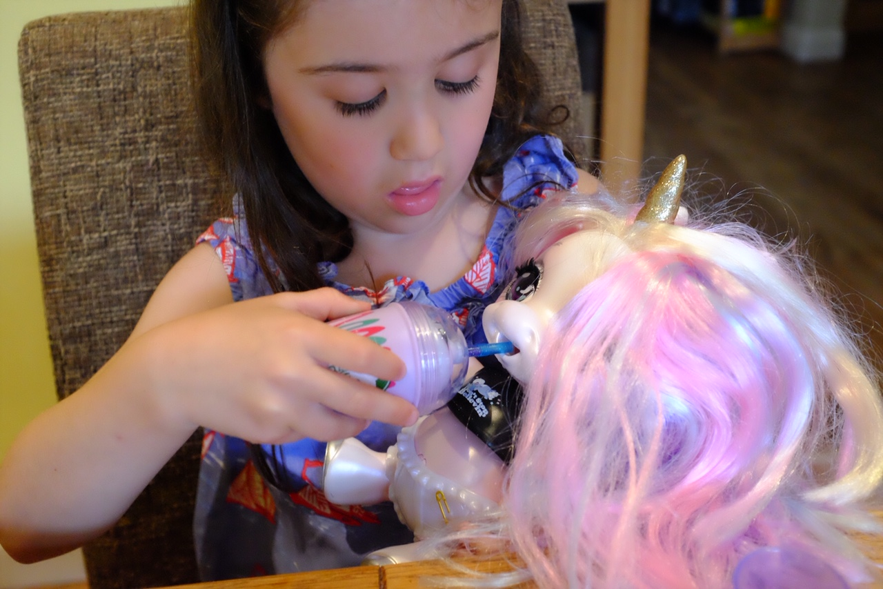 girl feeding the Poopsie slime surprise unicorn