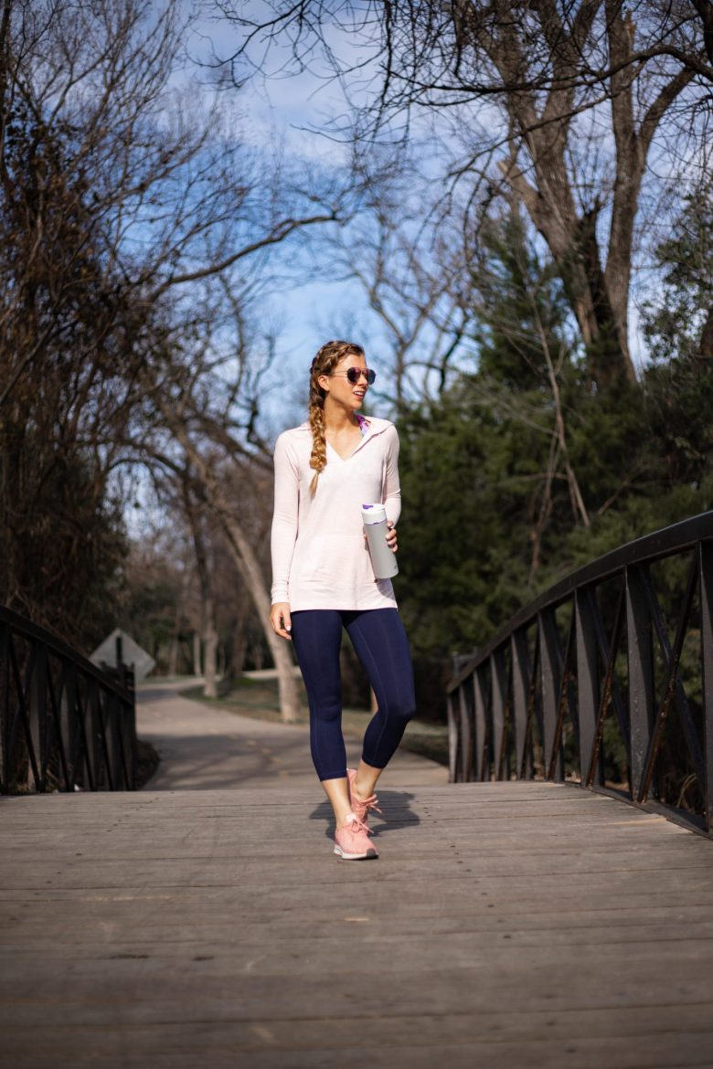 Kasey Goedeker of Running in Heels runs across a bridge at White Rock Lake wearing a light pink Lilly Pulitzer hoodie and navy blue Zella leggings. Her shoes are the pink Nike Pegasus 35 and she carries an Astrea water bottle with filter.