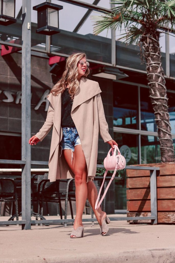 spray tan misconceptions with Palm Beach Tan | Running in Heels | blonde girl wears denim shorts, black lace up cami, and camel open coat with neutral mules