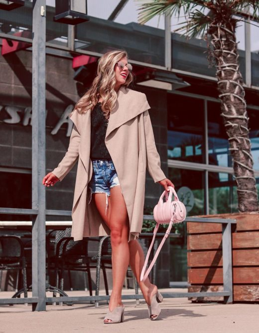 spray tan misconceptions with Palm Beach Tan   Running in Heels   blonde girl wears denim shorts, black lace up cami, and camel open coat with neutral mules