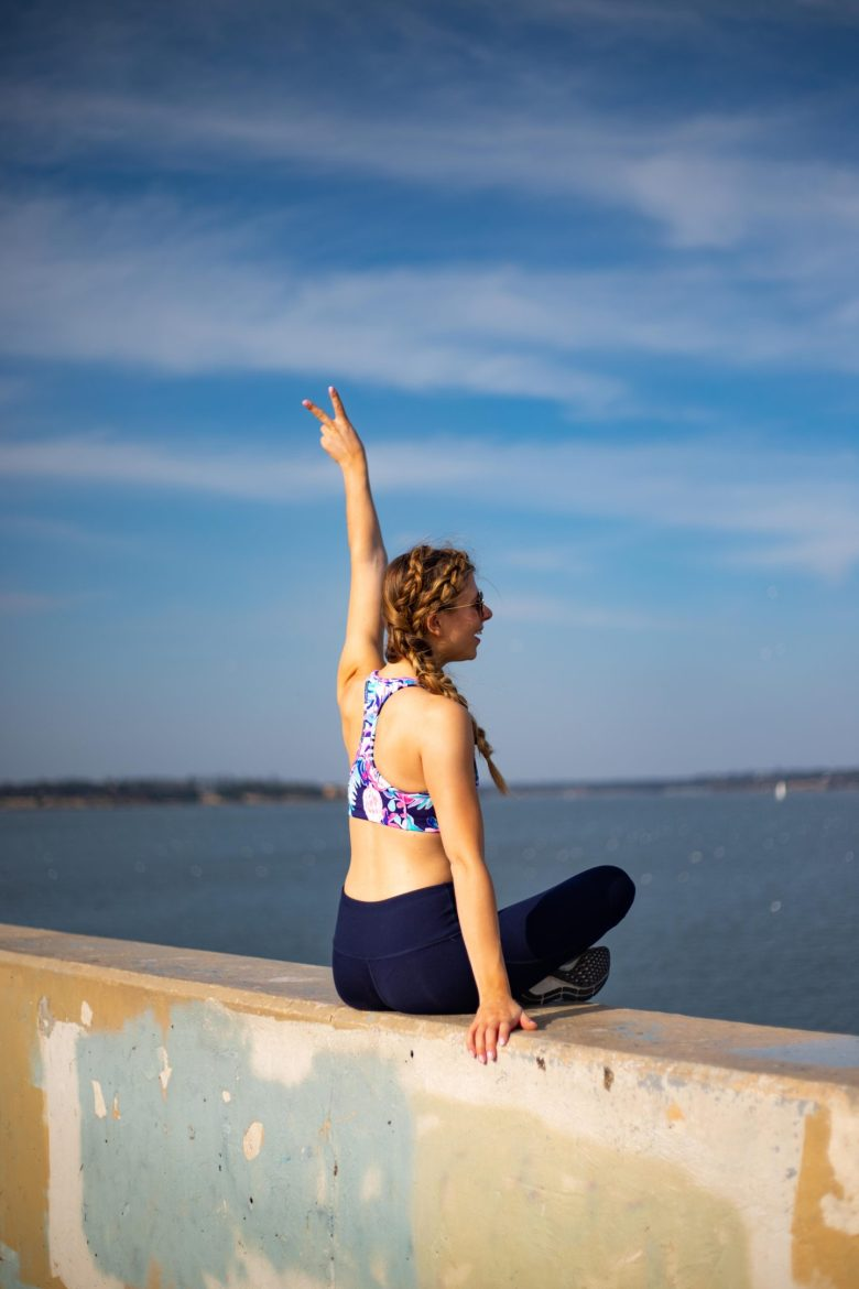 7 reasons to get a spray tan, featured by top US beauty blog, Running in Heels: Kasey Goedeker sits on ledge overlooking White Rock Lake in activewear by Zella and a Lily Pulitzer sports bra with a spray tan.