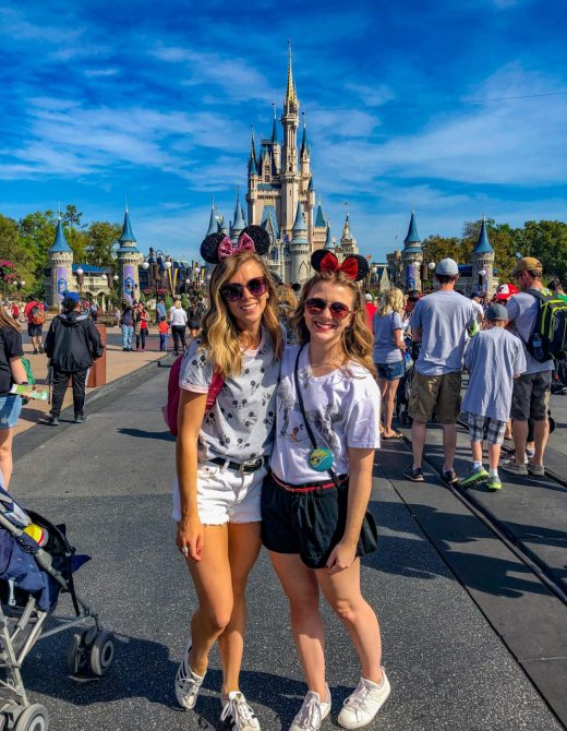 Adult Guide to Disney World Theme Parks Broken Down by Park | Running in Heels | Two sisters stand in front of the castle in Magic Kingdom wearing casual summer looks with minnie mouse ears.