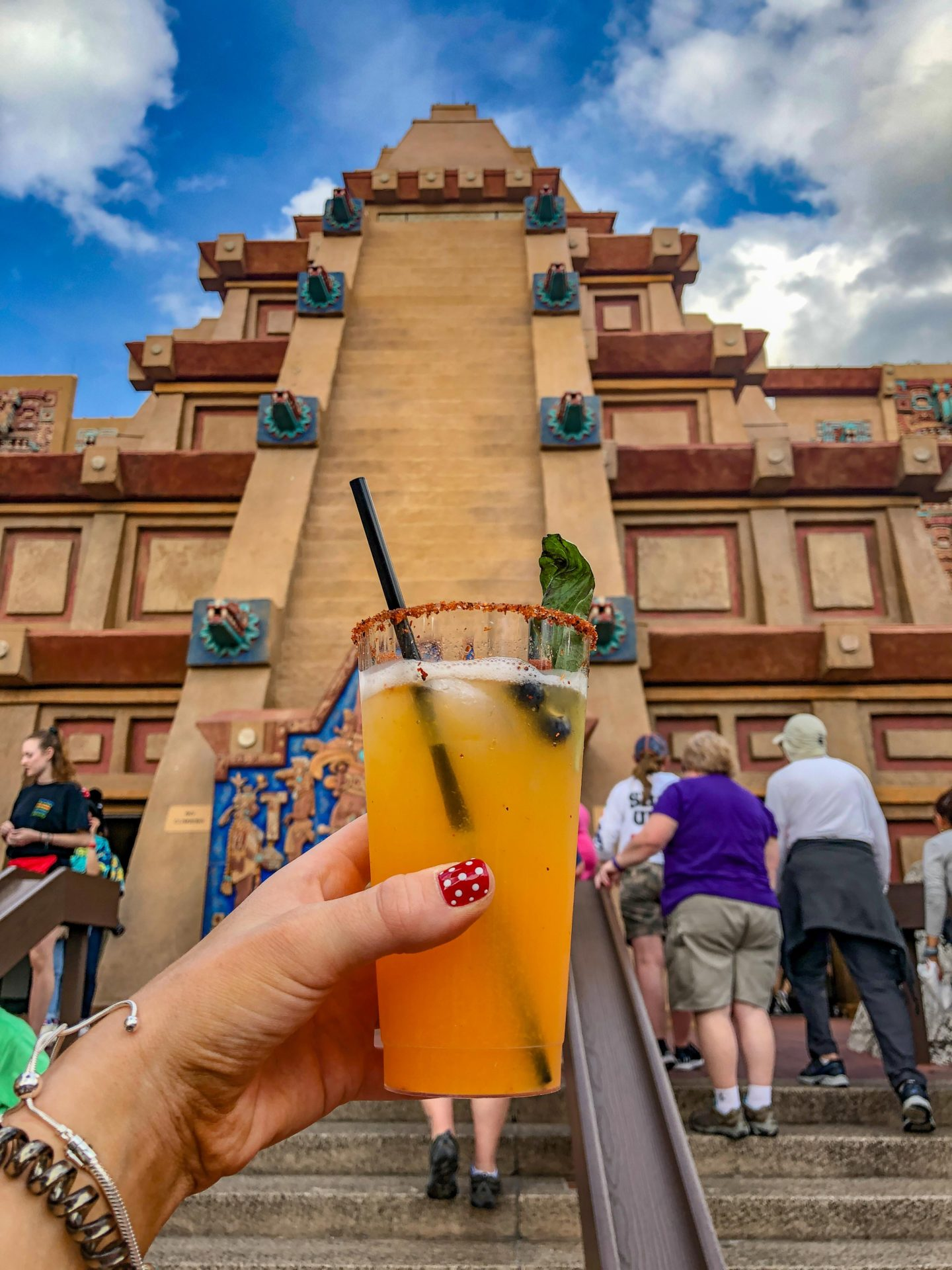 Adult Guide to Disney World Theme Parks Broken Down by Park | Running in Heels | Kasey holds a Maelstrom (Mango Habanero) Margarita in front of the Mexico pavilion in Epcot World Showcase in Disney World.