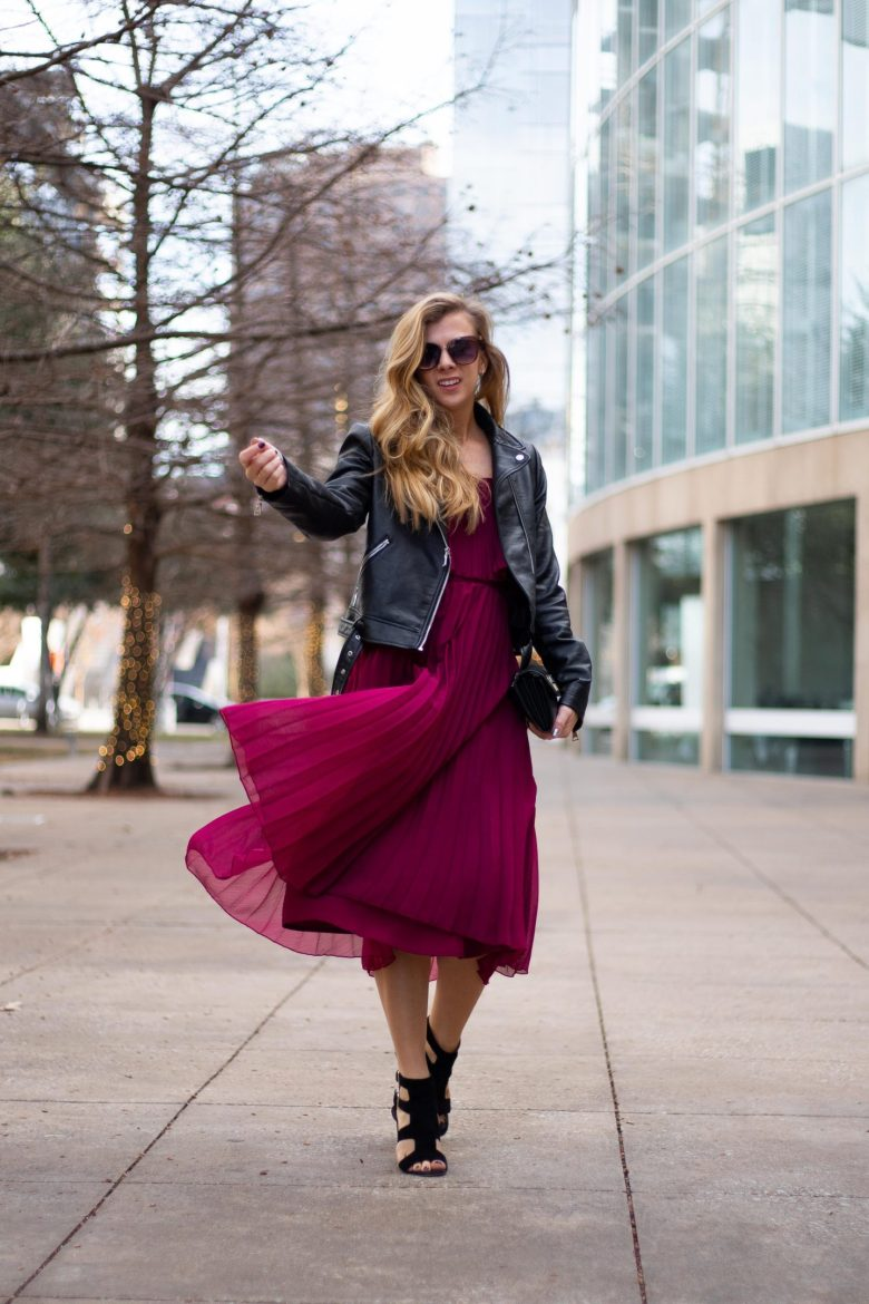 Kasey Goedeker of Running in Heels blog walks downtown wearing a pleated burgundy dress with a black faux leather moto jacket