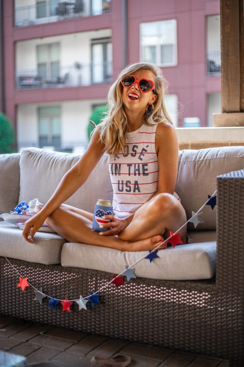 Cute 4th of July outfits featured by top US fashion blog, Running in Heels: image of a woman wearing a 4th ion July graphic tank, Target heart sunglasses, Hari Mari flip flops and Levi's 501 shorts