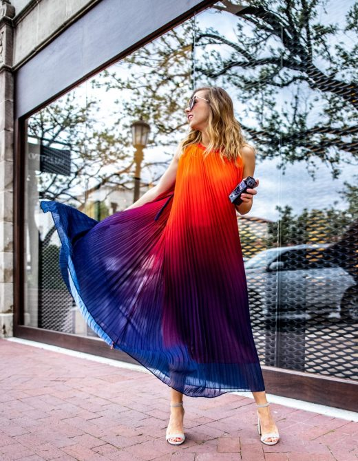 Kasey wears a Chicwish obmre dress that fades from orange to purple to blue on the bottom. It is perfect for a beach day! She's holding the sensuous smelling L'alique Amethyst Exquise fragrance sold at Neiman Marcus.