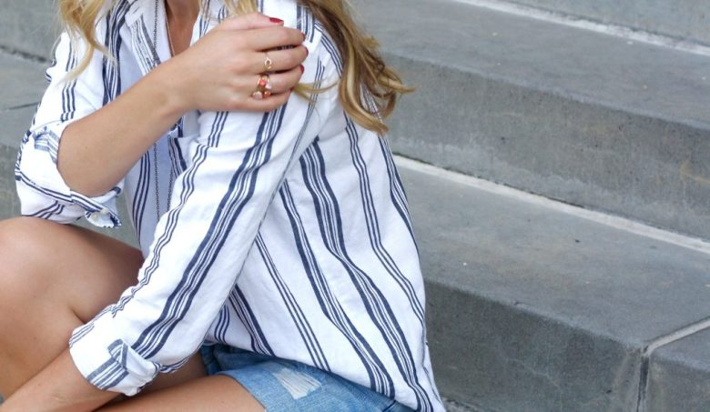 Why wear long sleeves in the Summer, tips featured by top US fashion blog, Running in Heels: image of a woman wearing a striped button down shirt with denim shorts