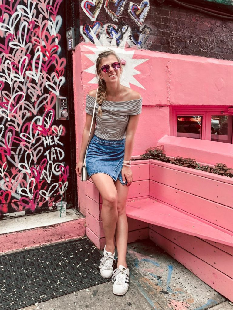 Where to eat in NYC, Pierto Norte, Pink as Fuck, girl sits on the pink outside of the pink cafe