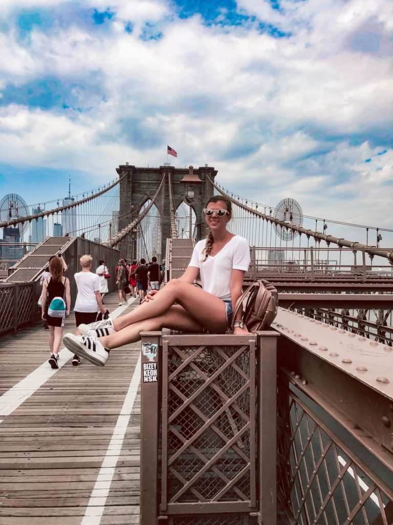 Things to do in NYC in the summer when you've already been there   Girl sits onthe Brooklyn Bridge   What to wear in NYC in the Summer   Summer outfits   Travel outfit